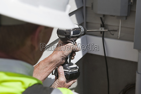 communications worker drilling access hole through