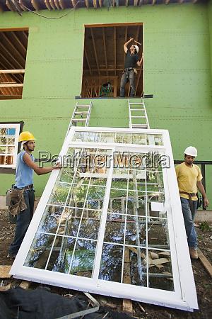 carpenters preparing to hoist window frame