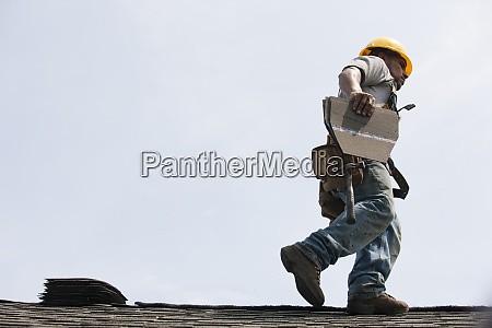roofer working on shingling a new