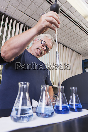 engineer pipetting water sample and indigo