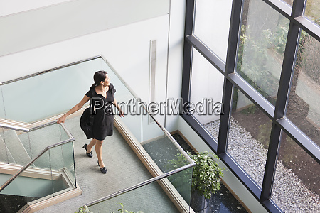 hispanic businesswoman with briefcase on stairs