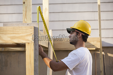 hispanic carpenter measuring deck joist using