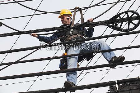 communications worker adding cables to a