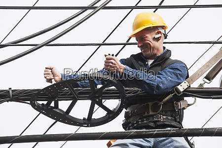 communications worker using a wrench on