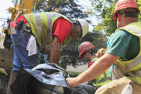 construction workers preparing for excavator to