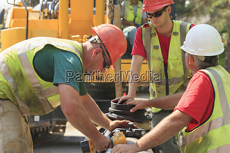construction workers using battery powered wrench