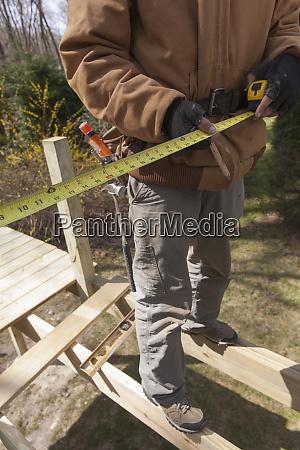 hispanic carpenter standing on deck joists
