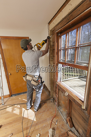 hispanic carpenter using reciprocating saw to