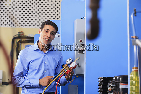 student demonstrating air conditioner recharging manifold
