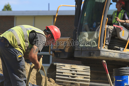 construction engineer removing excavator suspension strap