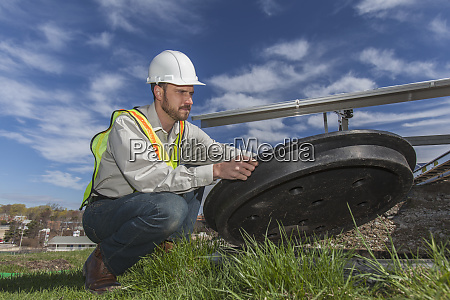 power engineer opening inspection hatch at