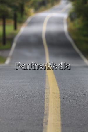 vanishing roadway with yellow line in
