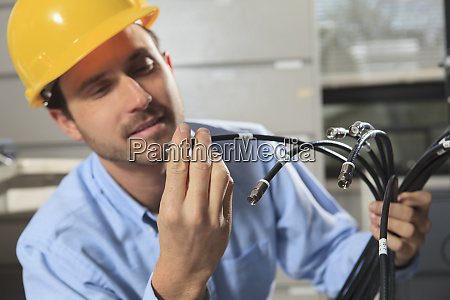 network engineer examining cable termination connector