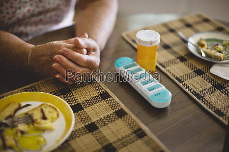 senior woman with pill case on