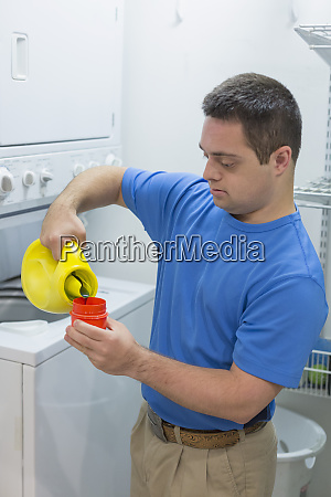 man with down syndrome pouring laundry
