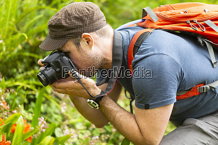 a man photographing flowers in a