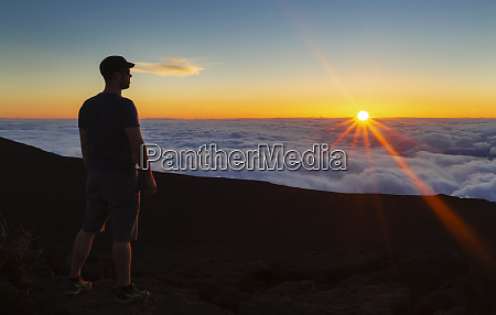 silhouetted man standing on rock above