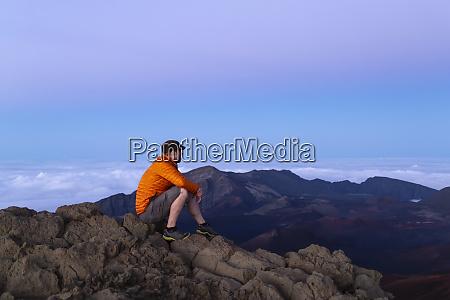 tourist sits on a mountain summit