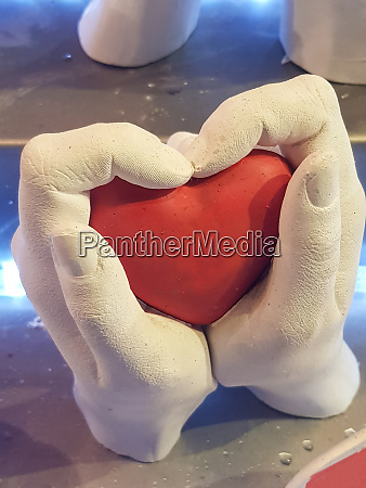 two hands enclose a heart