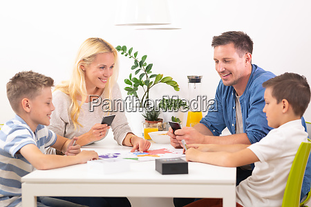 happy young family playing card game