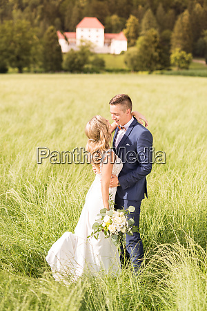 newlyweds hugging tenderly in meadow in
