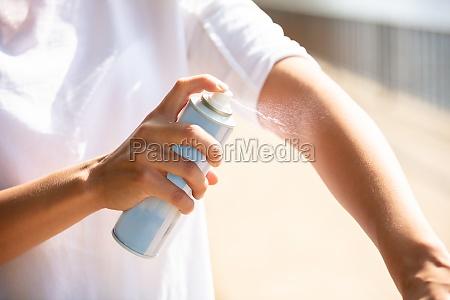 woman spraying anti insect deet spray