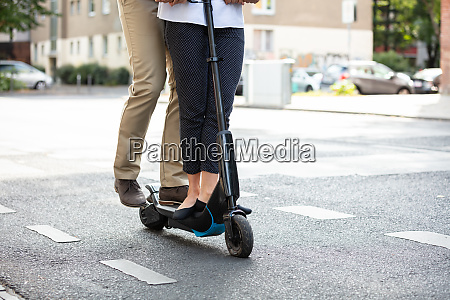 couples standing on electric scooter over