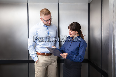 businesswoman discussing with businessman in elevator