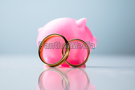 pink piggy bank with wedding rings