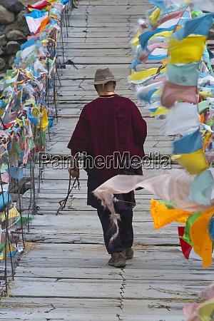 tibetan man walking on hanging bridge