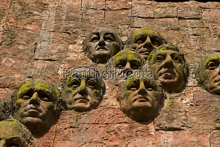 close up of faces on facade