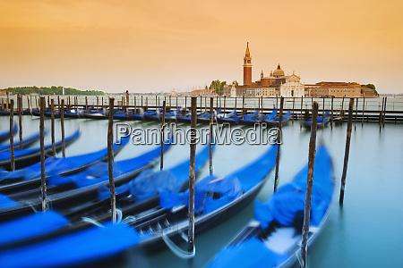 italy venice moored gondolas and church
