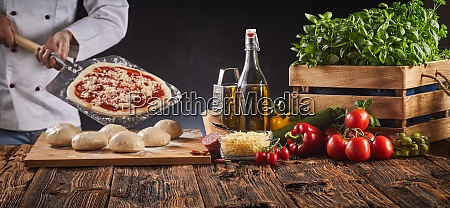 chef in a pizzeria preparing an