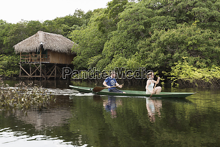 tourists canoe in the amazon river