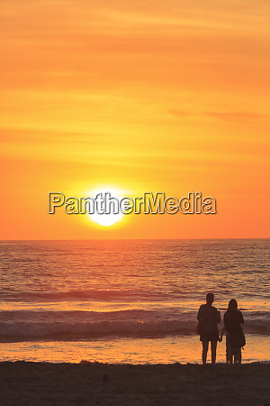 couple in silhouette pacific beach sunset