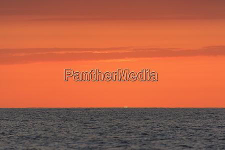 green flash sun setting on ocean