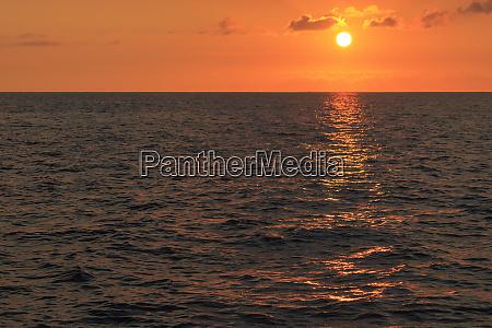 sun setting on ocean off maui