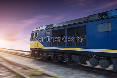 fast freight blue train at sunset