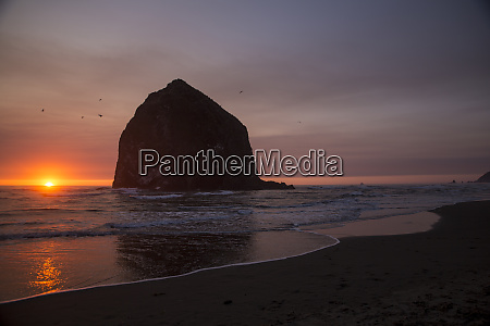 cannon beach oregon glowing sunset dips