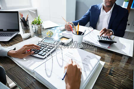 two business colleagues calculating tax