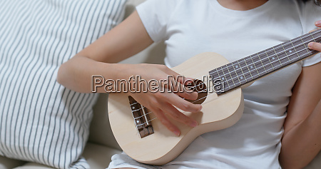 woman practice ukulele at home