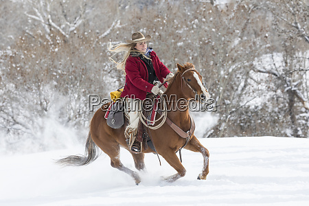 cowgirl riding her horse wintertime hideout