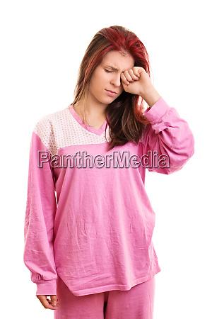 sleepy girl in pink pajamas rubbing
