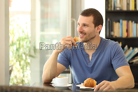 happy man eating a croissant for