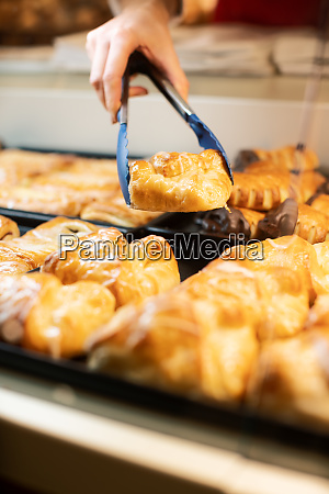 woman selling fresh pastries in bakery
