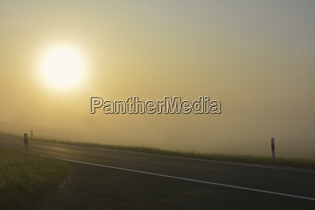 road in fog at sunrise with