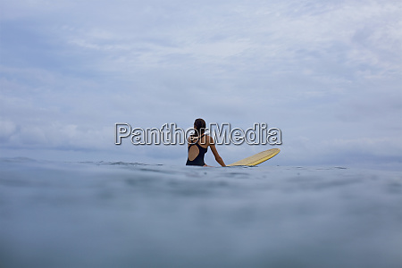 female surfer straddling surfboard in ocean