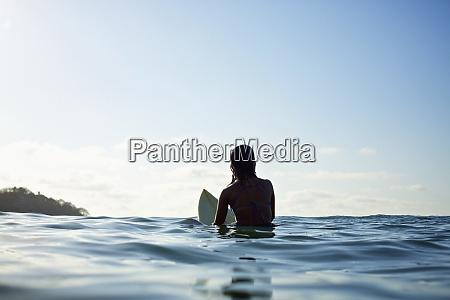 silhouette female surfer straddling surfboard waiting
