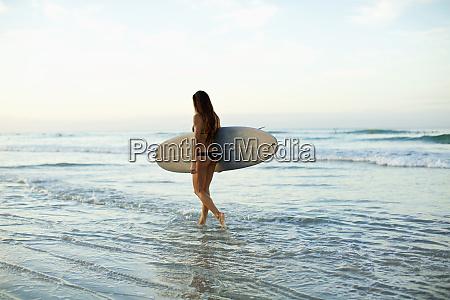 female surfer carrying surfboard in ocean