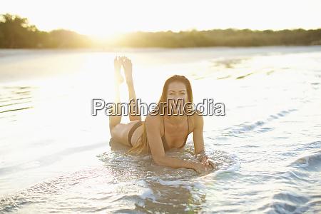portrait woman in bikini laying in